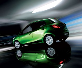 Mazda 2 Lime Green Side And Rear Angle Moving Wallpaper